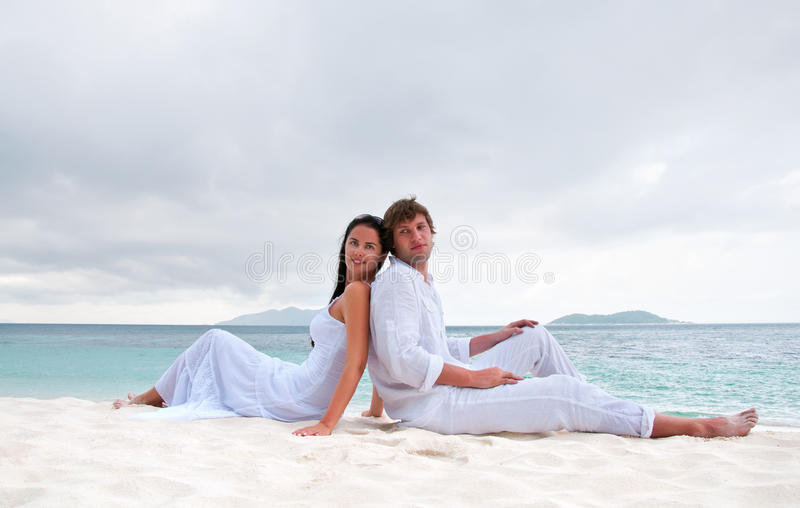 Jonge paarzitting op het strand dichtbij de kust royalty-vrije stock foto
