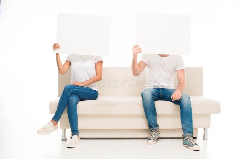 'jonge paarzitting op witte bank en het verbergen van hun gezichten door lege die banners, op wit worden geïsoleerd royalty-vrije stock afbeelding