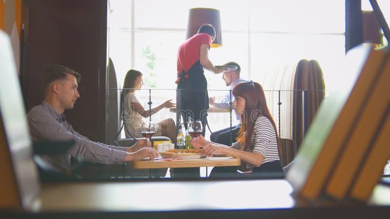 Jonge paarzitting in restaurant die en het drinken wijn spreken stock afbeelding