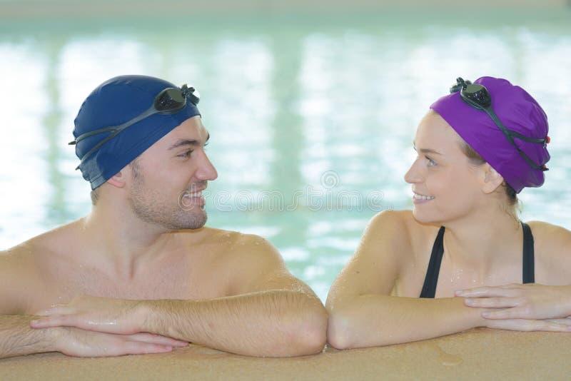 Jonge paarzwemmers binnen zwembad stock foto's