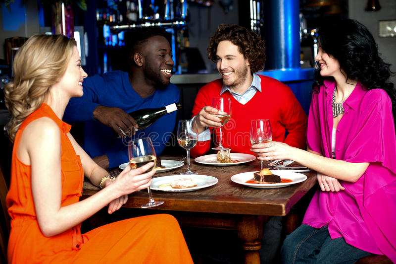 Jonge paren die van hun diner met dranken genieten royalty-vrije stock afbeelding