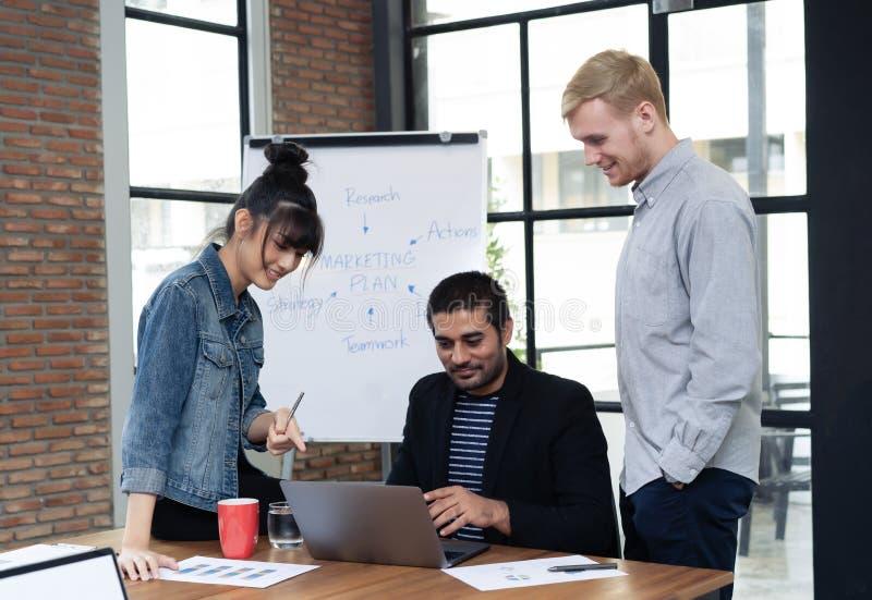 Jonge partners die ideeën of nieuw project in modern bureau bespreken terwijl het bekijken laptop Het schaak stelt bischoppen voo stock foto