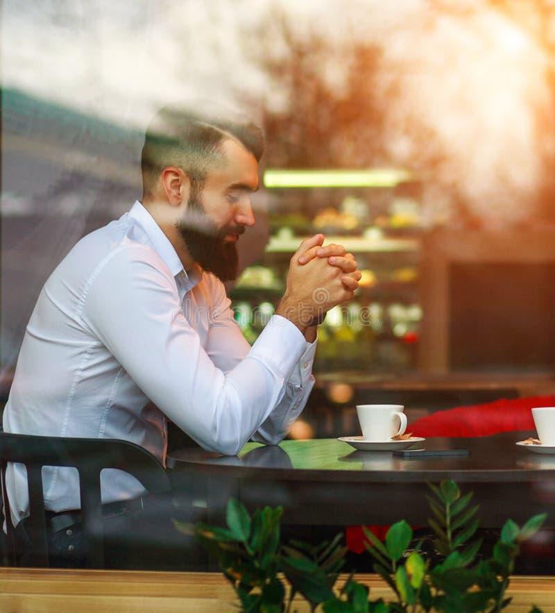 Jonge peinzende dromerige mannelijke zakenman die zorgvuldig in koffiemening door venster met bezinningen over glas mediteren stock foto