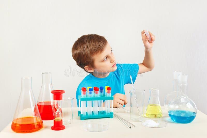Jonge peinzende jongen die chemische experimenten in laboratorium doen stock afbeelding
