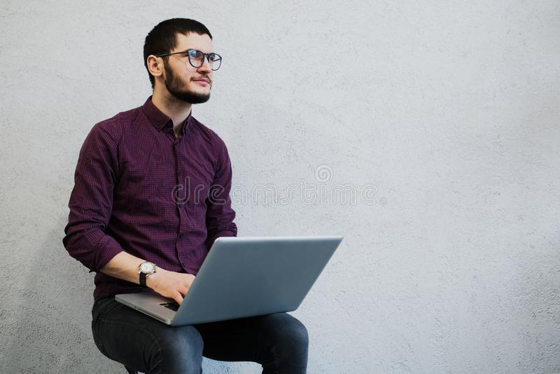 Jonge peinzende kerel die laptop met behulp van, die glazen op achtergrond van wit dragen royalty-vrije stock fotografie