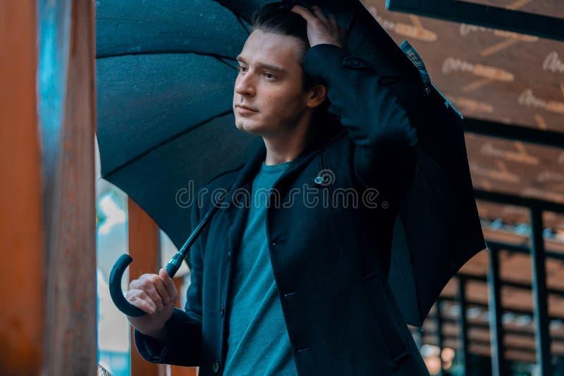 Jonge peinzende knappe mens die met paraplu op regenachtige dag in park lopen stock afbeelding