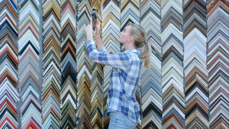 Jonge peinzende vrouwelijke cliënt die een kader, het kiezen zoeken, die foto met digitale tablet in atelier nemen royalty-vrije stock fotografie