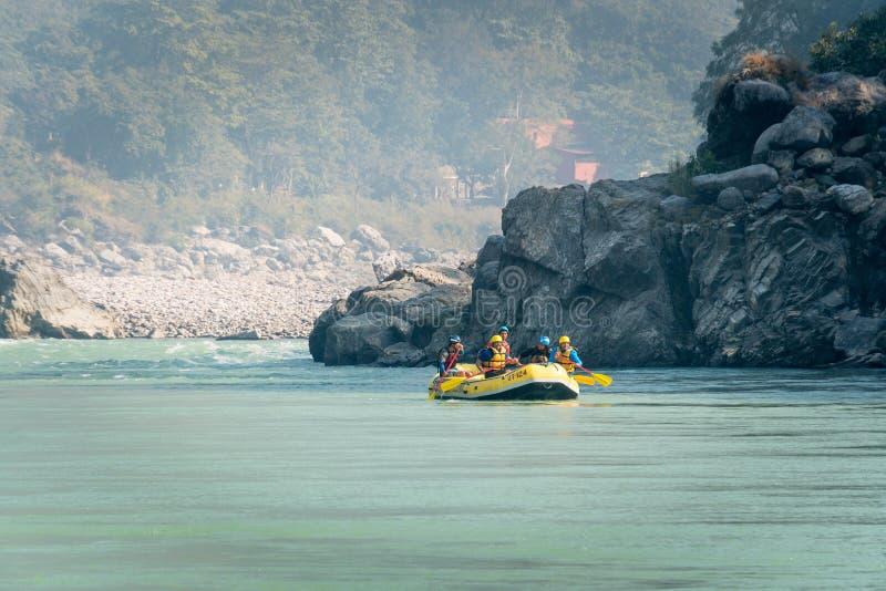 Jonge personen die op de rivier van Ganges in de sport van Rishikesh, van het uiterste en van de pret bij toeristische attractie  stock afbeeldingen