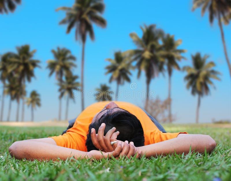 Jonge persoon het ontspannen in een tuin op gazon stock foto's