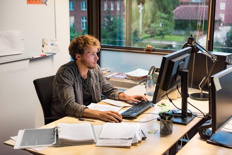 Jonge phd student die het schrijven definitief document voor examen bestuderen bij universiteit Werkende mens bij bureau het type stock fotografie