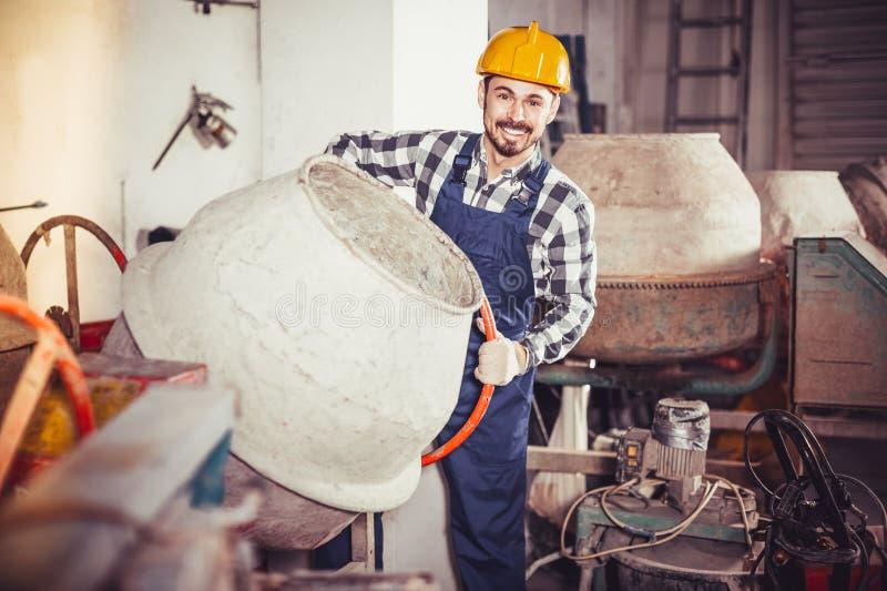 Jonge positieve arbeider die concrete mixer met behulp van stock afbeeldingen