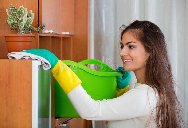 Jonge positieve langharige vrouw die regelmatige schoonmaak doen stock foto's