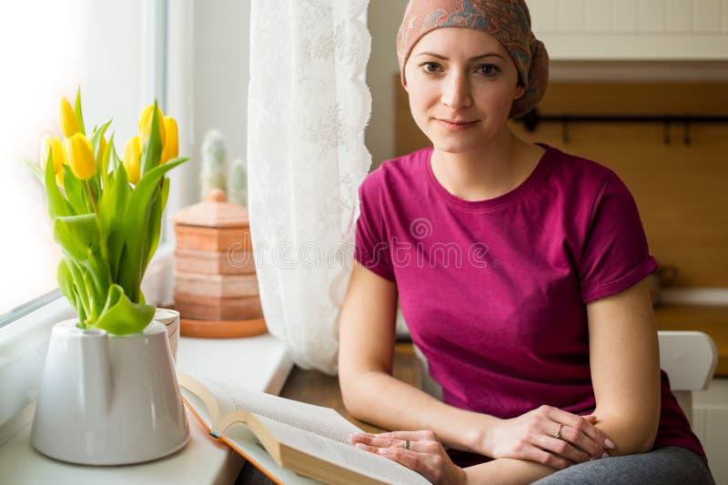 Jonge positieve volwassen vrouwelijke kanker geduldige zitting in de keuken door een venster die een boek, het glimlachen lezen stock afbeeldingen
