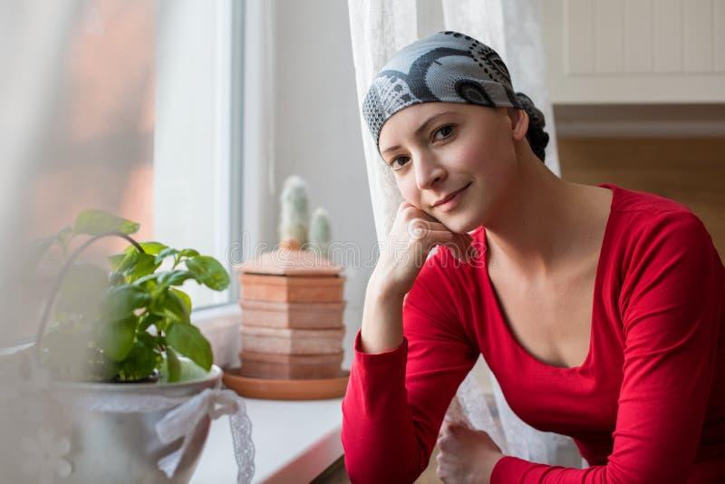 Jonge positieve volwassen vrouwelijke kanker geduldige zitting in de keuken door een venster, het glimlachen royalty-vrije stock afbeeldingen