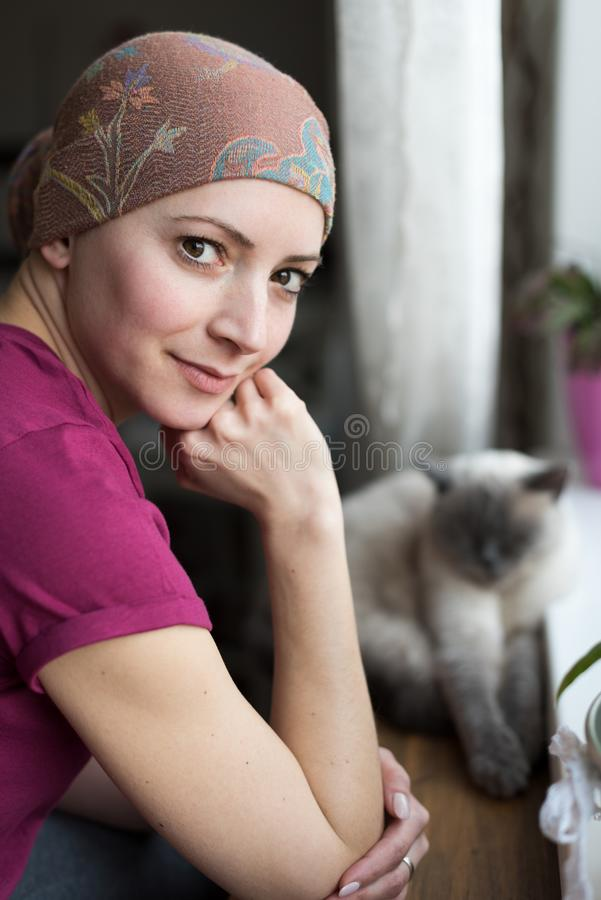 Jonge positieve volwassen vrouwelijke kanker geduldige zitting in de keuken door een venster met haar huisdierenkat, het glimlach royalty-vrije stock foto's