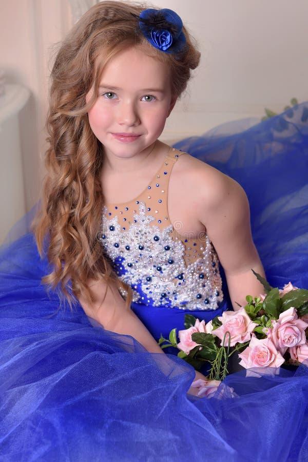 Jonge prinses in een blauwe avondjurk met rozen en een weinig blauwe hoed royalty-vrije stock foto's