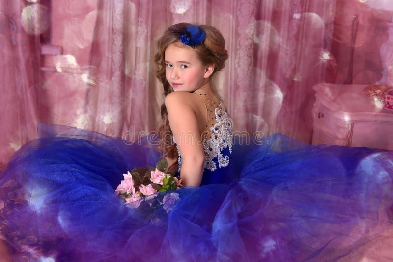 Jonge prinses in een blauwe avondjurk met rozen en een weinig blauwe hoed stock afbeelding