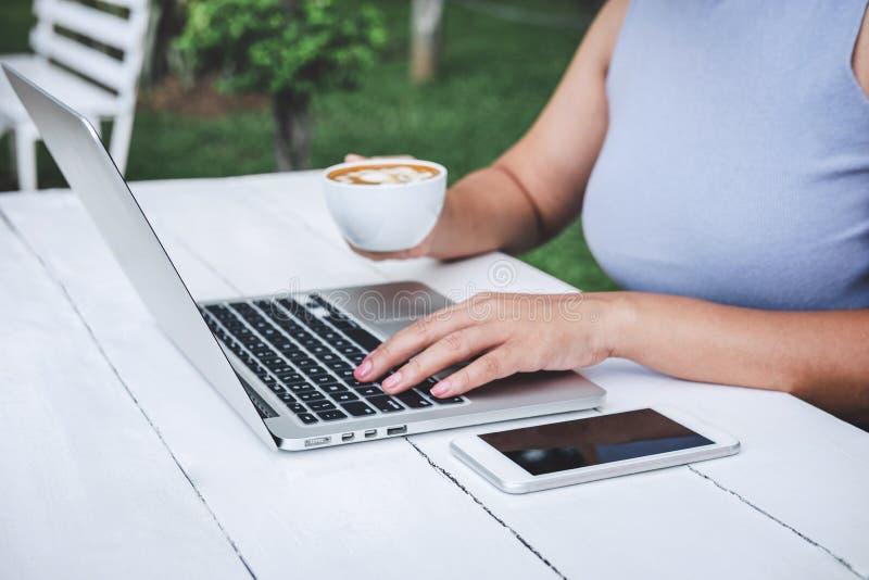 Jonge professionele vrouw die in slimme vrijetijdskleding gebruikend laptop in openluchtwerkplaats, houdend een kop van koffie en stock foto