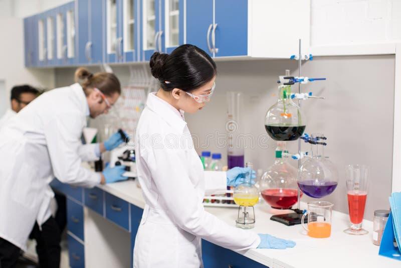Jonge professionele wetenschappers die experiment in onderzoeklaboratorium maken royalty-vrije stock foto