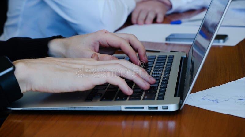 Jonge professionele zakenman die zwarte col dragen en moderne laptop, Close-up met behulp van van mannelijke handen die typen stock foto