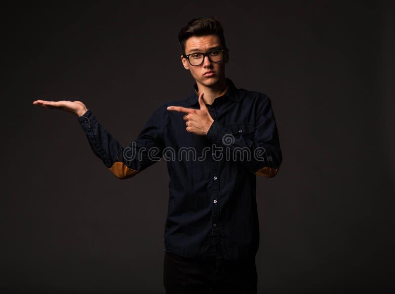 Jonge raadselachtige mens die door handen tonen royalty-vrije stock afbeeldingen