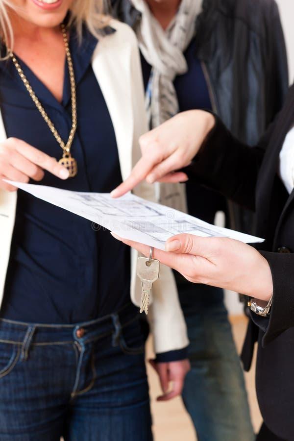 Jonge realtor verklaart te koppelen huurovereenkomst stock afbeelding