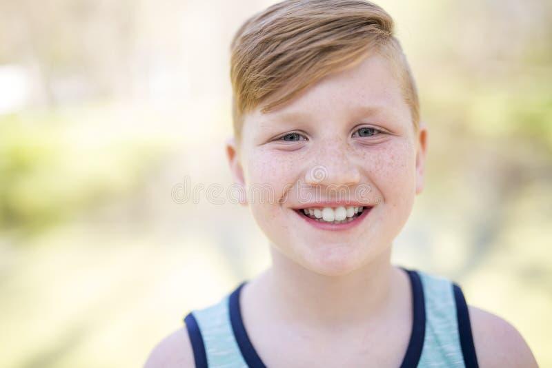 Jonge redheaded jongen die buiten spelen stock foto's