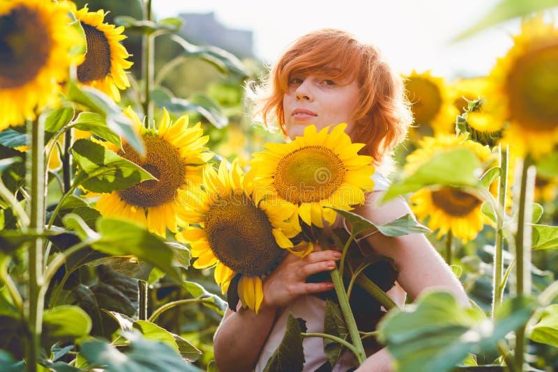 Jonge redheaded vrouw die op het gebied van zonnebloemen een reusachtige bos van bloemen in een zonnige de zomeravond houden stock foto