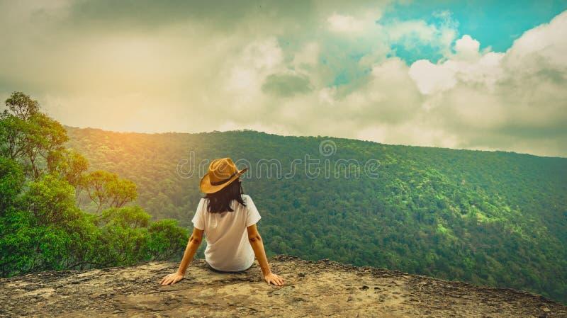 Jonge reizende vrouw die hoed dragen en op de bovenkant van de bergklip zitten met het ontspannen van stemming Aziatische vrouwen stock afbeeldingen