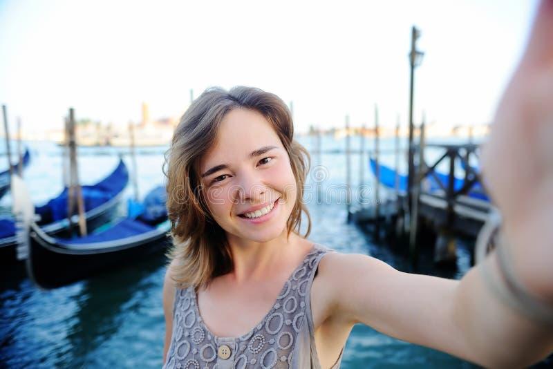 Jonge reiziger die selfie foto met gondels op de achtergrond in Venetië, Italië maken stock foto's