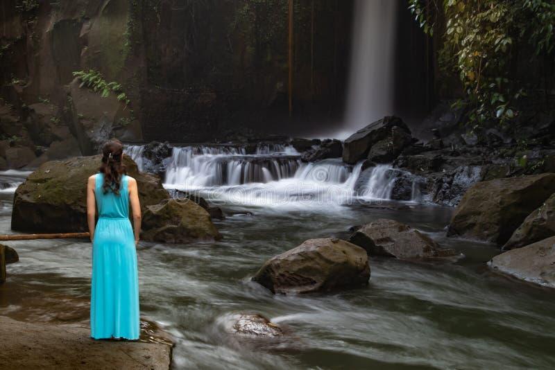 Jonge reizigersvrouw bij waterval in tropisch bos, Ubud, Bali Sumampanwaterval Mening van rug Langzame blindsnelheid, motie stock afbeelding