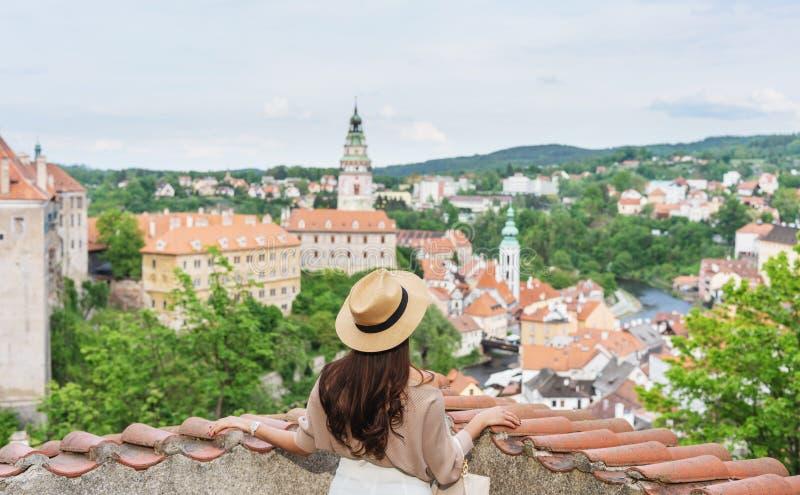 Jonge reizigersvrouw die in hoed stadsmening bekijken van Cesky Krumlov, Tsjechische Republiek in de zomer stock foto
