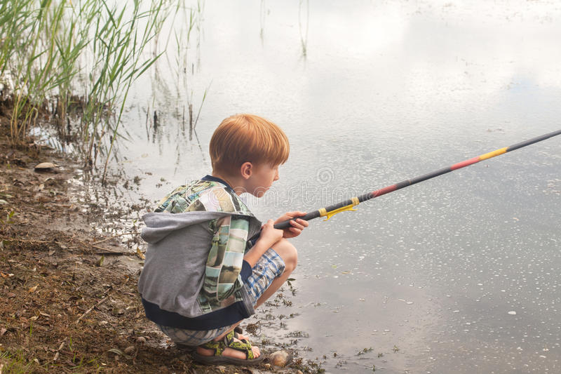 Jonge, rode haarjongen die in een meer vissen royalty-vrije stock fotografie