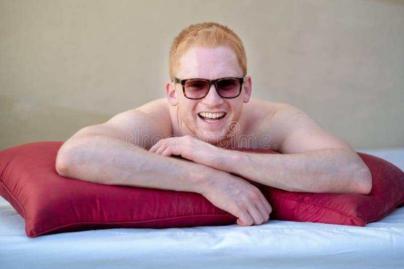 Jonge rode haired mens die met zonnebril in de zitkamer glimlachen stock afbeelding