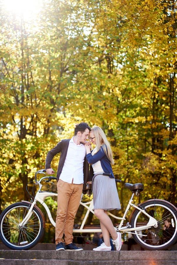 Jonge romantische paar gebaarde man en aantrekkelijke vrouw bij fiets achter elkaar in de herfstpark of bos royalty-vrije stock foto's