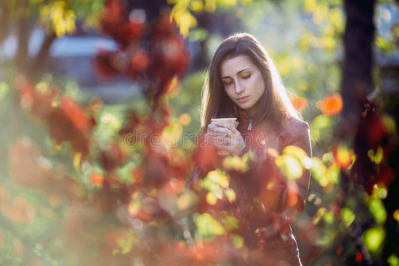 Jonge romantische vrouw in bruin leerjasje over achtergrond de herfstportret Het mooie meisje stellen in park met kop van coffe F stock foto's