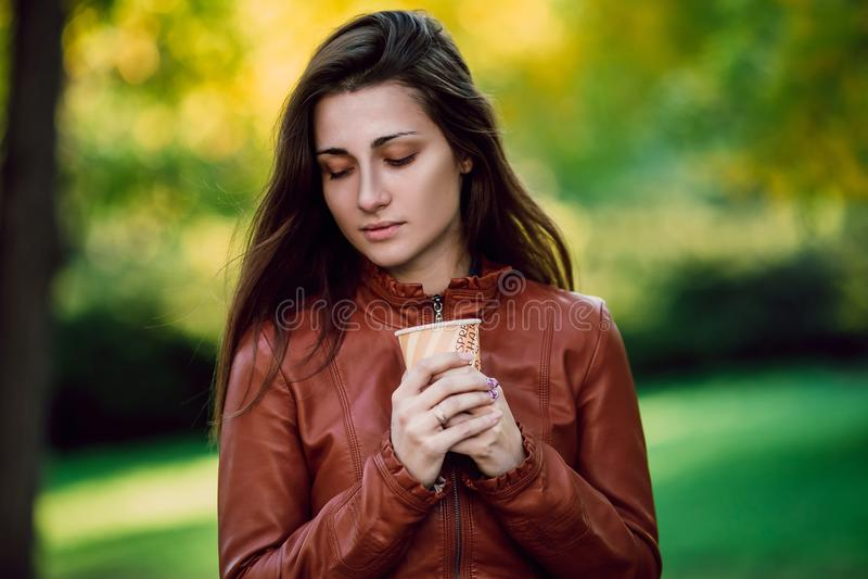 Jonge romantische vrouw in bruin leerjasje over achtergrond de herfstportret Het mooie meisje stellen in park met kop van coffe F royalty-vrije stock fotografie