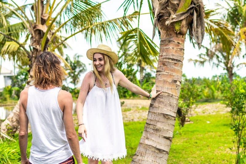 Jonge romatic paartoerist onder de kokospalm Heldergroen en geel beeld Het eiland van Bali indonesië stock afbeeldingen