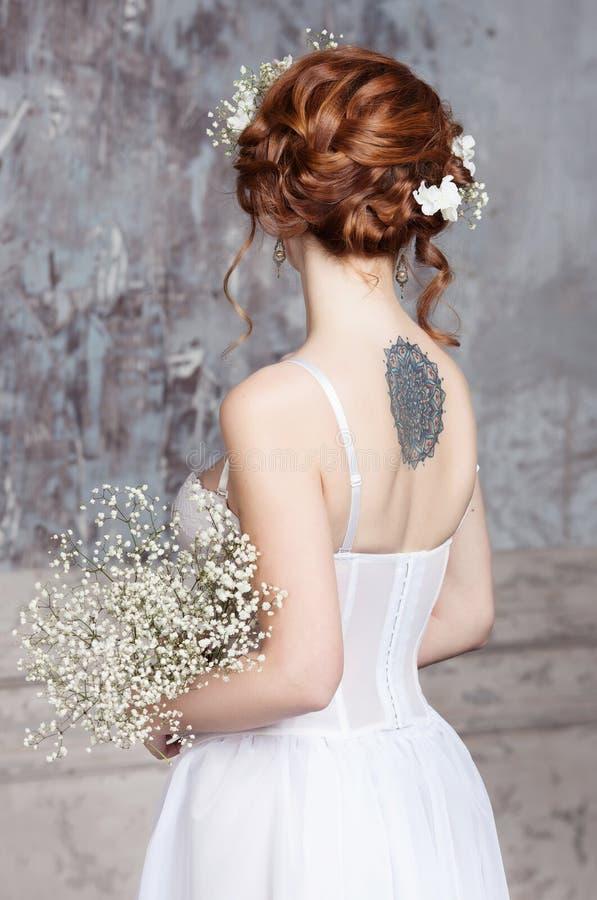 Jonge roodharige bruid in elegante huwelijkskleding Zij bevindt zich met haar terug naar de kijker royalty-vrije stock afbeeldingen