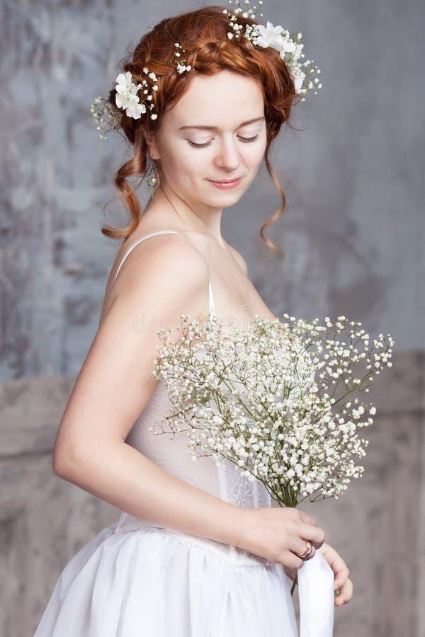 Jonge roodharige bruid in elegante witte huwelijkskleding Zij bevindt zich, zijn haar ogen dromerige gesloten, royalty-vrije stock foto