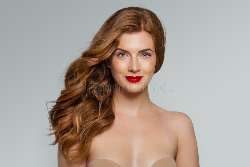 Jonge roodharige glimlachende vrouw tegen witte muurachtergrond royalty-vrije stock foto's