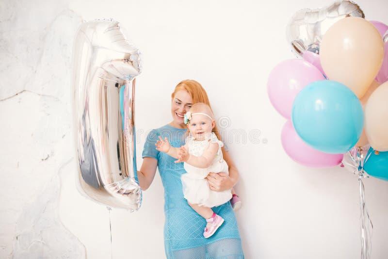 Jonge roodharige moeder die een babymeisje één jaar in een kleding op een witte achtergrond thuis houden Het concept een kinderen stock foto's