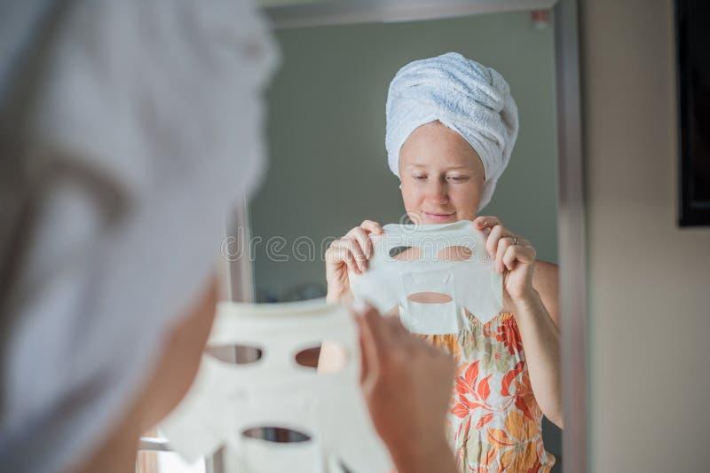 Jonge roodharige vrouw die gezichtsmaskerblad doen stock fotografie