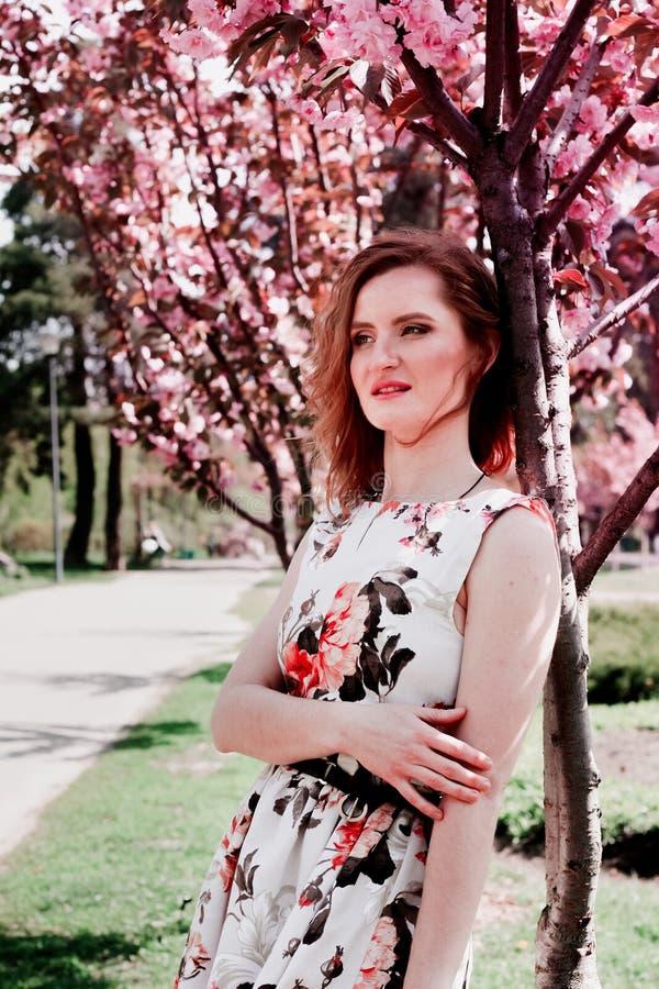 Jonge Roodharigevrouw in de tuin van de lentebloemen De lente Sakura royalty-vrije stock foto