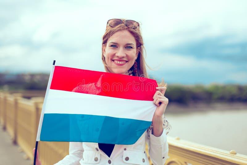 Jonge roodharigevrouw die Nederlandse vlag op brug houden royalty-vrije stock afbeelding