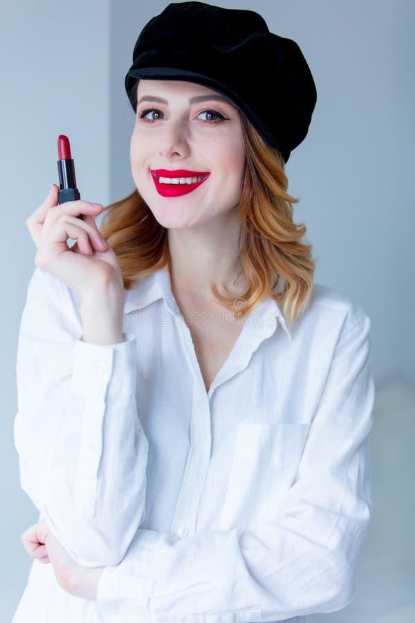 Jonge roodharigevrouw in hoed met lippenstift voor make-up royalty-vrije stock afbeelding