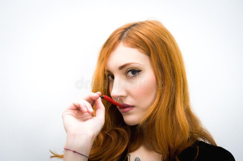 Jonge roodharigevrouw met het roodgloeiende portret van de Spaanse peperpeper stock afbeelding