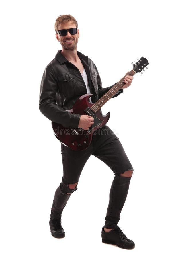 Jonge rotsster die bij gitaar en het glimlachen presteren royalty-vrije stock afbeeldingen