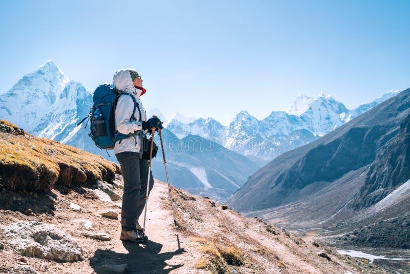Jonge rugzak-vrouwtje met een wandeling met trekpolen tijdens het hoogtepunt van de Everest Base Camp-route nabij Dingboche, royalty-vrije stock afbeelding