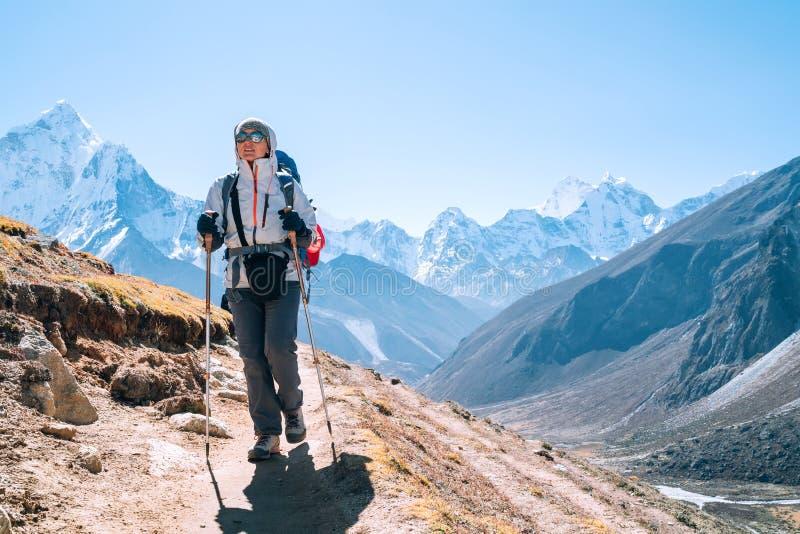 Jonge rugzak-vrouwtje met een wandeling met trekpolen tijdens het hoogtepunt van de Everest Base Camp-route nabij Dingboche, stock afbeeldingen